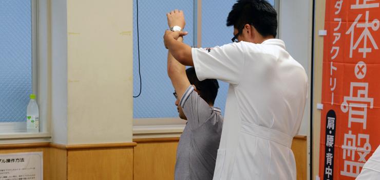踊り手の肩の可動域を広げてパフォーマンスの向上をはかる、塩田スタッフ