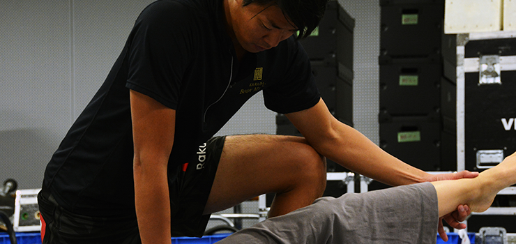 下肢のストレッチを行う堤トレーナー